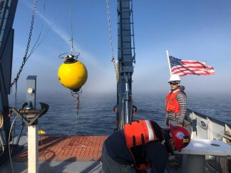 : Image courtesy of researcher Jay Austin. Technician Craig Hill and Marine Tech Jason Agnich prepare to deploy an acoustic current meter in Lake Superior; the data is stored in the Data Repository for University of Minnesota (DRUM).
