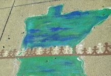 Sidewalk chalk drawing of state of Minnesota with a line of brown and white stick figure people across the state.