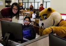 Alicia Kubas, left, and Goldy help out a student on History Day at Wilson Library.